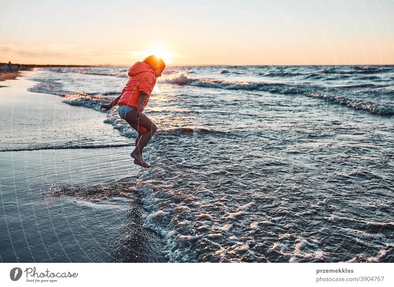 Verspieltes kleines Mädchen, das bei Sonnenuntergang am Sandstrand über die Meereswellen springt aufgeregt frei genießen positiv Emotion sorgenfrei Natur