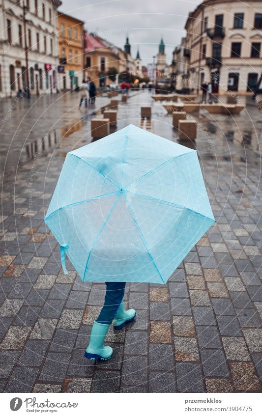 Kind hält großen blauen Regenschirm in der Hand und geht an einem verregneten, düsteren Herbsttag durch die Innenstadt im Freien wenig saisonbedingt fallen