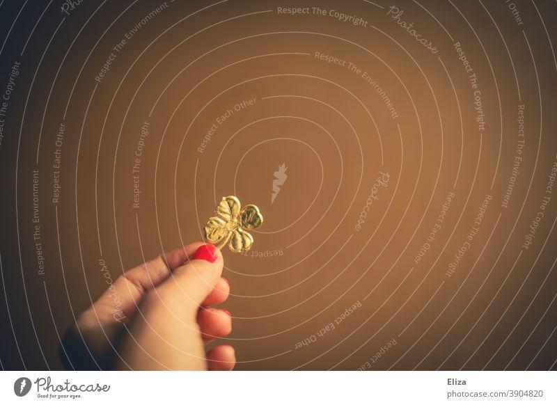 Hand hält ein goldenes vierblättriges Kleeblatt. Glücksbringer zu Silvester fürs neue Jahr. Glücksklee Jahreswechsel Glück bringen Glück wünschen Neujahr