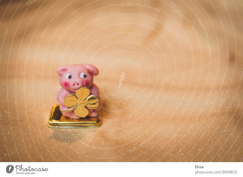 Glücksschwein aus Marzipan mit goldenem vierblättrigem Kleeblatt. Glück fürs neue Jahr zu Silvester. Schwein Neues Jahr Glücksbringer Silvester u. Neujahr