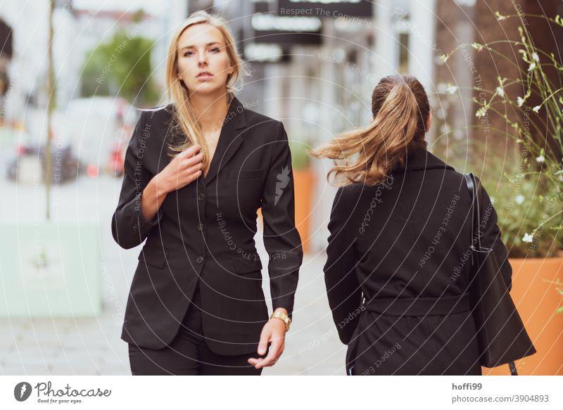 die junge Frau geht und blickt selbstbewusst in die Kamera Junge Frau Karriere Erfolg lächelnde Frau Lifestyle Mode elegant Frauengesicht Blick in die Kamera
