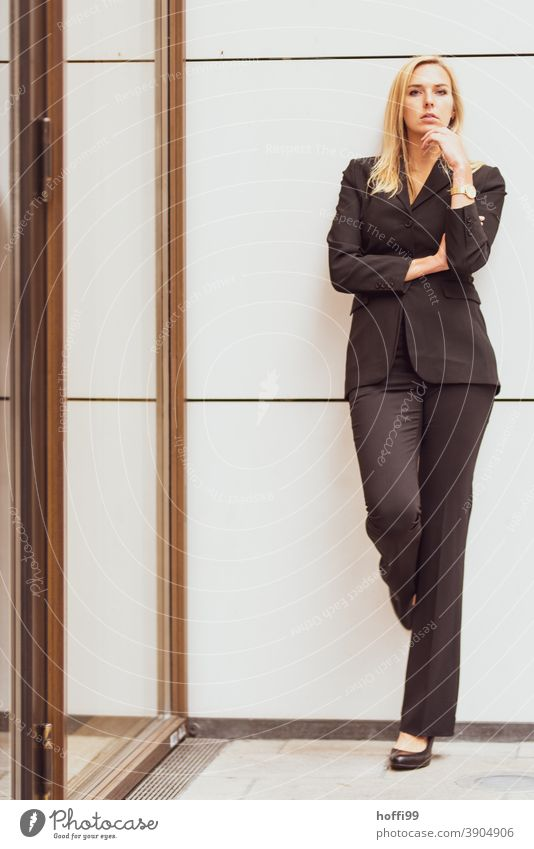 die junge Frau, angelehnt an eine Wand, blickt selbstbewusst in die Kamera Junge Frau Karriere Erfolg lächelnde Frau Lifestyle Mode elegant Frauengesicht
