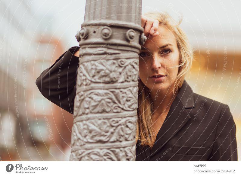 die junge Frau blickt, lässig an eine Säule gelehnt, in die Kamera Junge Frau lächelnde Frau Lifestyle Mode elegant Frauengesicht Blick in die Kamera feminin
