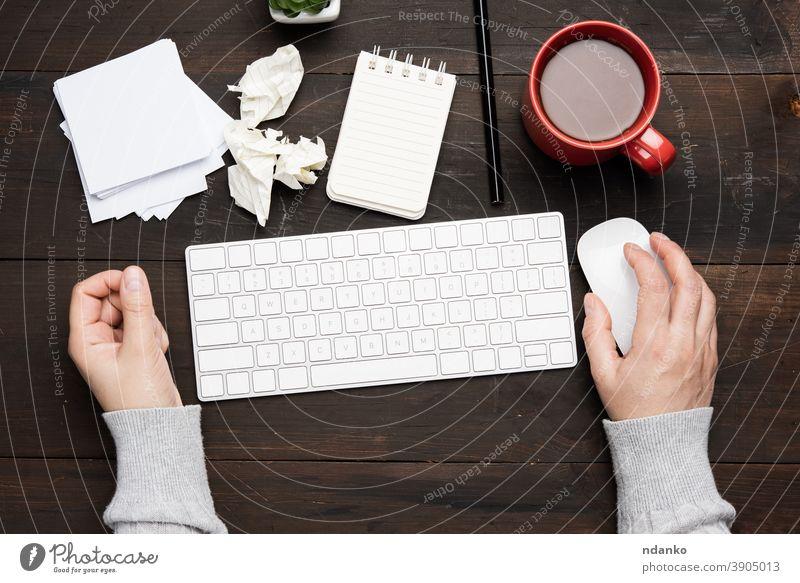 weiße drahtlose Tastatur und Maus auf einem braunen Holztisch, neben einer weißen Tasse mit Kaffee Business Keyboard Büro Computer Arbeitsplatz Kaukasier Hand