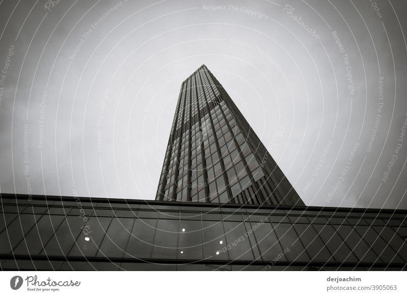 Architektur von hoher Qualität.  Ein Hochhaus ragt steil in den Himmel.  Mit ganz vielen Fenstern. Aufgenommen in Klassisch Schwarz  / Weiß.
