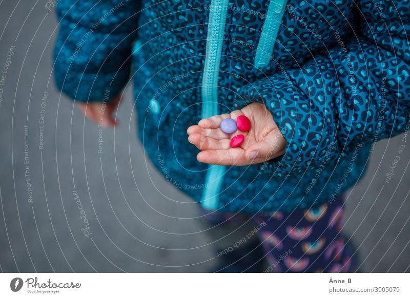 Kinderhand mit drei bunten Schokolinsen Smarties Schokoladen-Dragee Geschmack Süßwaren Appetit & Hunger Süßigkeit Lebensmittelfarbe unwiderstehlich Kindheit
