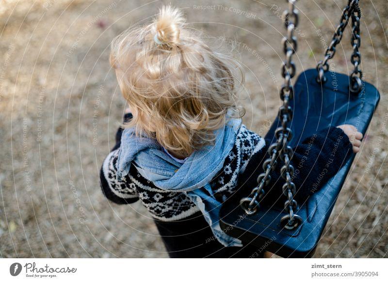 Kind mit Schaukel auf dem Spielplatz introvertiert waldorf Kinderkleidung Kindheit Spielen einsam traurig alleine zufrieden beobachten
