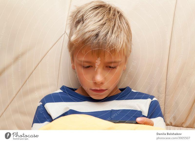 Kleines Kind spielt ein Spiel oder sieht sich etwas auf einem mobilen Smartphone an Bett Schlafenszeit Junge Kaukasier Handy Funktelefon Kindheit Mitteilung