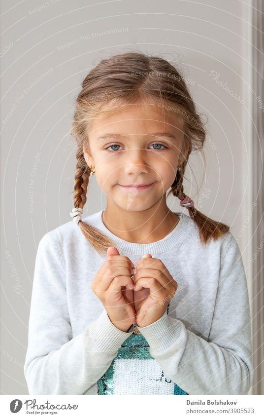 Porträt von niedlichen kleinen Mädchen zeigt Hand Herz Geste, süße kostbare Kind machen Körpersprache, Liebe, positive Gefühl und Emotion bezaubernd Waffen Baby