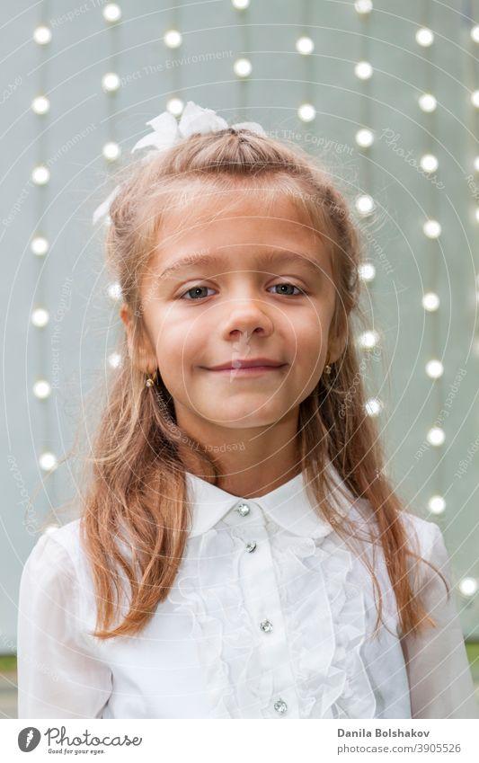 Porträt der niedlichen charmanten kleinen kaukasischen Mädchen in weißer Bluse und Bogen mit Hintergrund der leuchtenden Glühbirnen Menschen hell Unschärfe