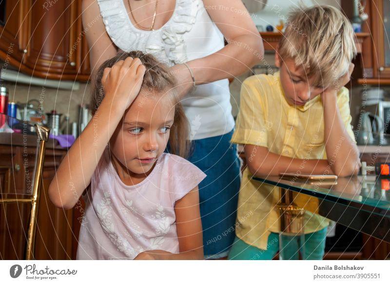 Mutter kämmt ihrer Tochter die Haare und flechtet sie, während der Junge im gelben Hemd über eine Videoverbindung mit dem Handy zu Hause kommuniziert Pflege