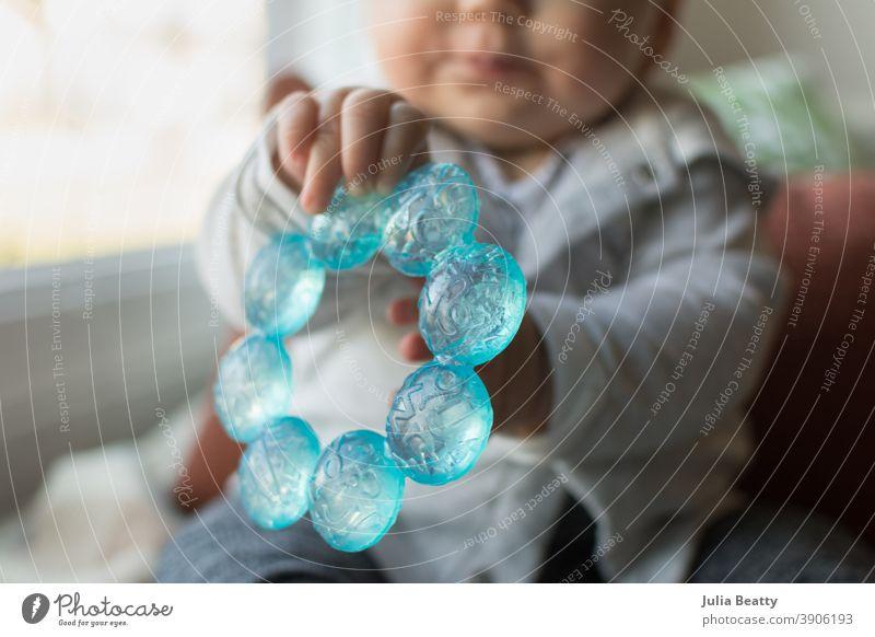 6 Monate altes Baby hält einen blauen Beißring in den Händen zahnend Kauen Zähne sechs Monate Säugling Halt packen erkunden sensorisch Wasser kalt Kunststoff