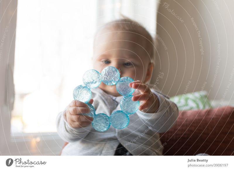 6 Monate halten Baby halten Beißring mit beiden Händen vor dem Gesicht Kauen Zähne sechs Monate Säugling Halt packen erkunden sensorisch Wasser kalt Kunststoff