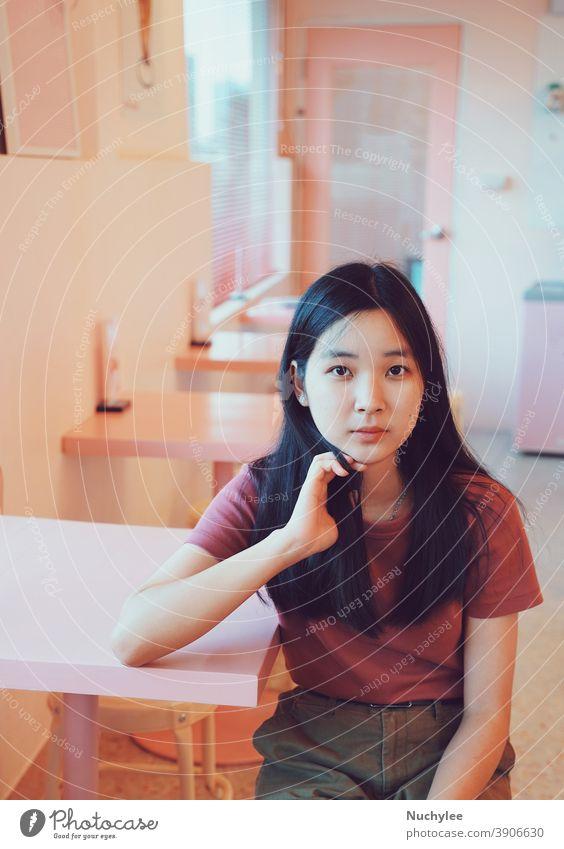 Junges asiatisches Teenager-Mädchen, süßes tausendjähriges Mädchen, das in die Kamera schaut und in einem pastellrosa Cafe sitzt, Lifestyle-Konzept Einsamkeit