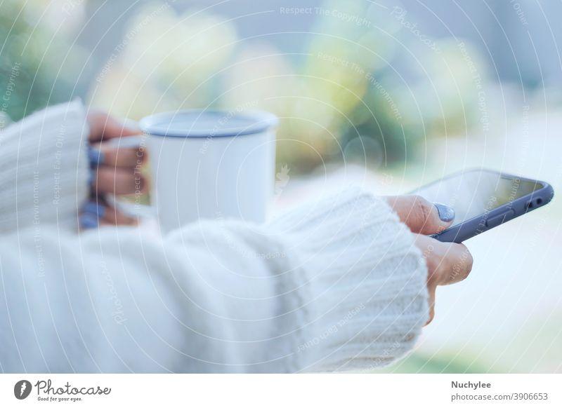 Nahaufnahme von Frauenhänden, die eine heiße Tasse Kaffee oder Tee halten und ein Smartphone im Hintergrund bei kaltem Wetter benutzen und warme, pelzbezogene Strickkleidung tragen