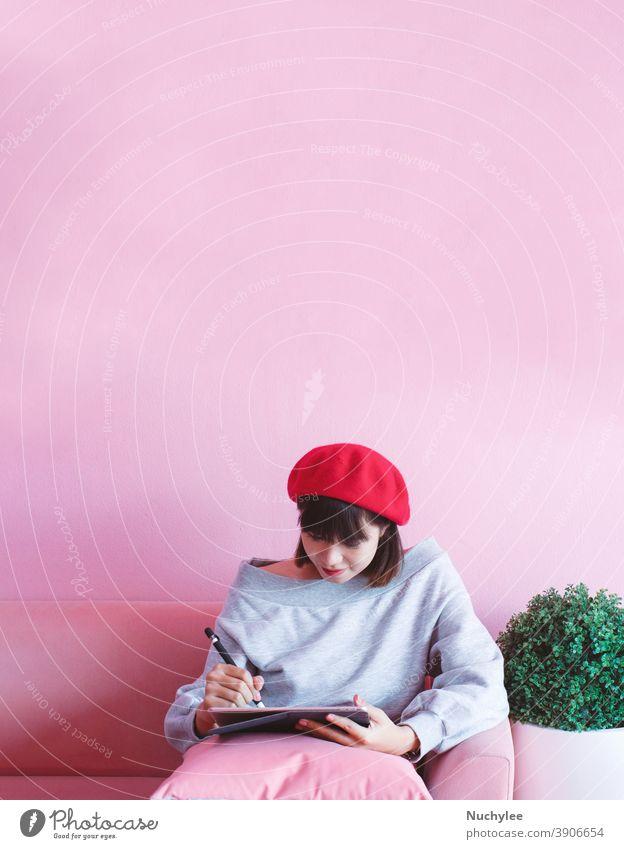 Junge asiatische tausendjährige Frau, die ein digitales Tablett im rosa pastellfarbenen Wohnzimmer benutzt und schreibt, Lifestyle- und Technologiekonzept