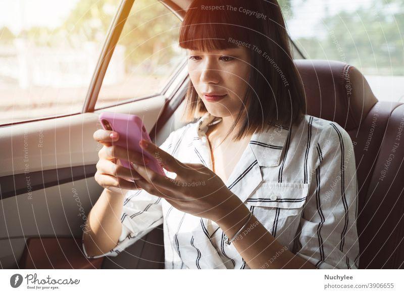 Junge asiatische Fahrgastfrau benutzt ihr Smartphone auf dem Rücksitz eines Autos, Transport- und Lifestyle-Konzept attraktiv Automobil Auto auf dem Rücksitz