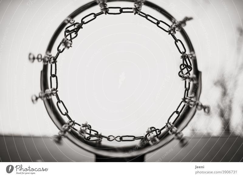 Basketballkorb von unten in schwarzweiß vor hellem Hintergrund | Gestell und Ketten aus Metall Basketballplatz Kettenglied Korb Hintergrund neutral