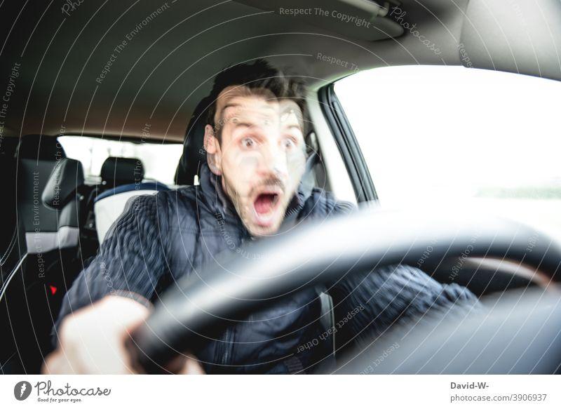 Unfallgefahr - Mann fährt mit dem Auto und tritt auf die Bremse Autofahren PKW Verkehrsunfall Straßenverkehr bremsen Reaktionszeit Unaufmerksamkeit Panik
