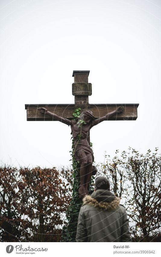 Mann steht vor einem alten Kreuz das von Kletterpflanzen umrankt ist Religion & Glaube Gott Vergessenheit Hoffnung Christliches Kreuz Jesus Christus beten
