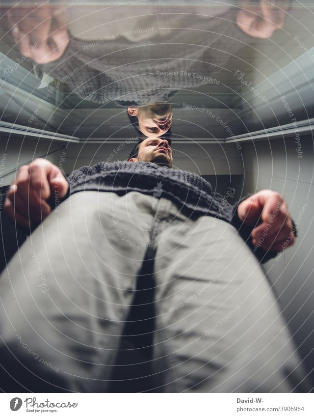 Mann schaut traurig durch die Scheibe nach draußen Depressionen Quarantäne Spiegelung Fensterscheibe coronavirus Corona einsam abstand Pandemie Infektionsgefahr