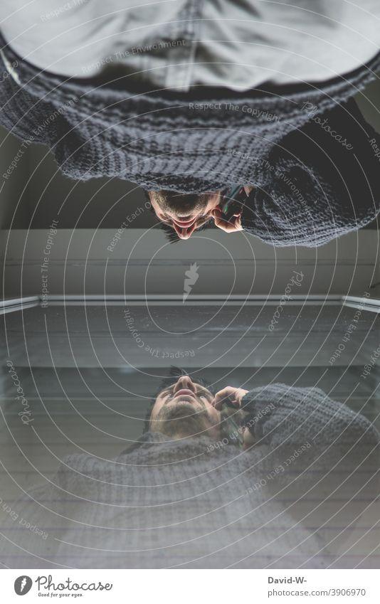 Mann mit Handy schaut durchs Fenster telefonieren Quarantäne Homeoffice zu Hause spiegelung Spiegelbild zu Hause bleiben ernst