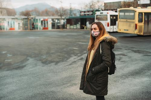 Frau mit Gesichtsmaske wartet am leeren Bahnhof auf den Bus 2019-ncov Auto-Bus Bosnien Busbahnhof Vorsicht Großstadt Stadtleben Korona Coronavirus covid-19