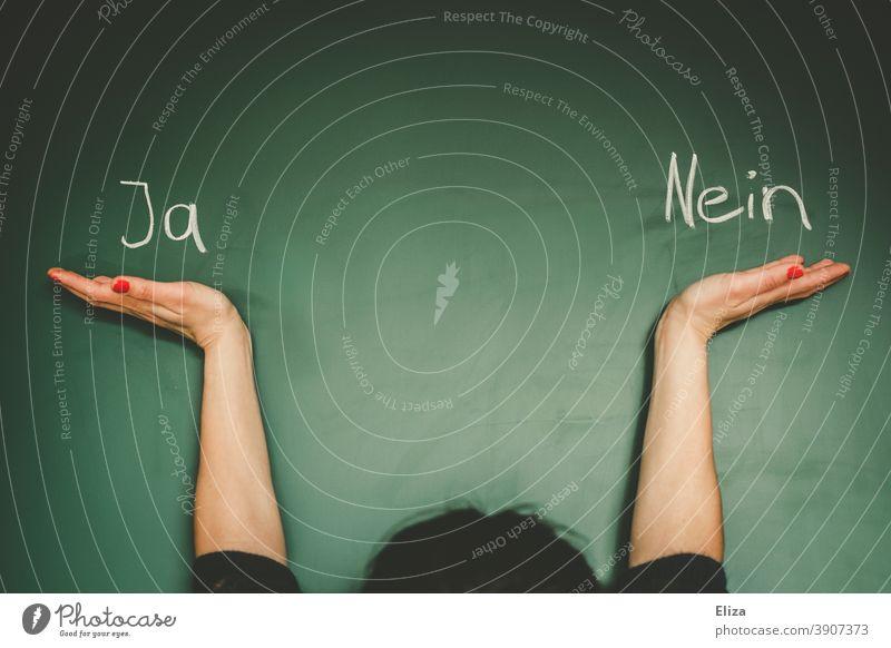 Frau wägt zwischen Ja und Nein ab. Wörter stehen auf einer Tafel. abwägen geschrieben unentschlossen Entscheidung Entscheidung treffen unsicher wählen