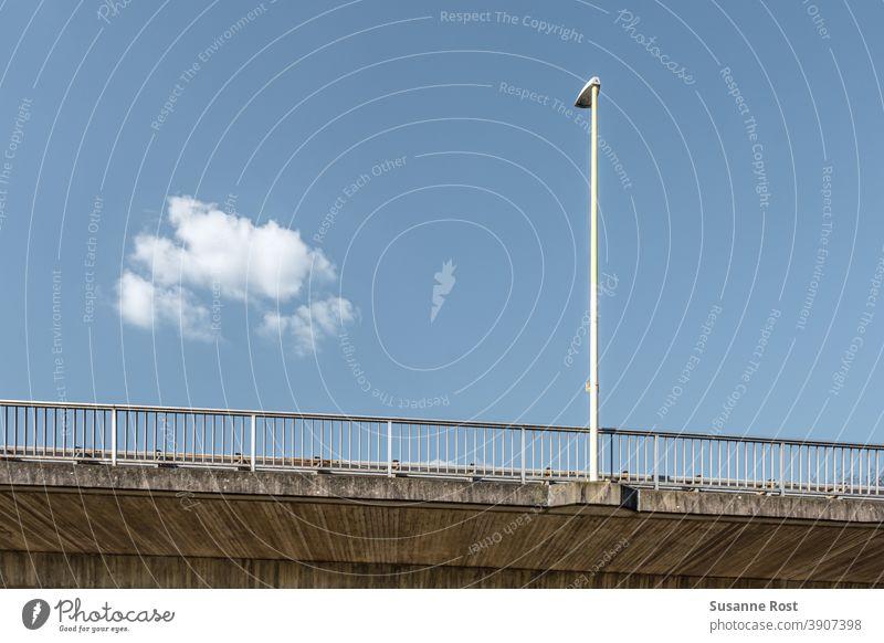 Laternenpfahl und Brückengeländer auf einer Brücke. Der Himmel ist blau, es gibt nur eine einzige Wolke. Geländer Architektur Tag Wolken Wolkenloser Himmel weiß