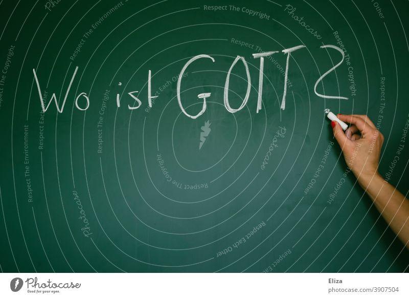 """Die Frage """"Wo ist Gott?"""" mit Kreide auf eine grüne Tafel geschrieben Religion Glauben Glaubensfrage gottlosigkeit wo wo ist gott Atheismus Agnostikerin Hand"""
