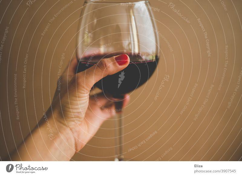 Weibliche Hand hält ein Glas Rotwein Alkohol Wein Prost trinken Weinglas Alkoholkomsum Frau Hintergrund neutral