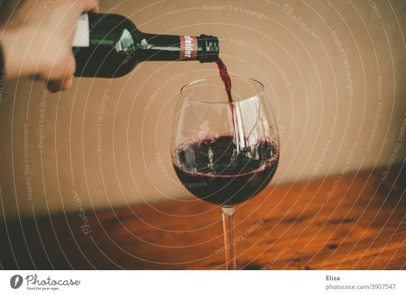 Person schenkt Rotwein aus einer Flasche in ein Weinglas ein gießen einschenken rot Glas Alkohol trinken Alkoholkonsum Weinflasche Rotweinflasche Rotweinglas