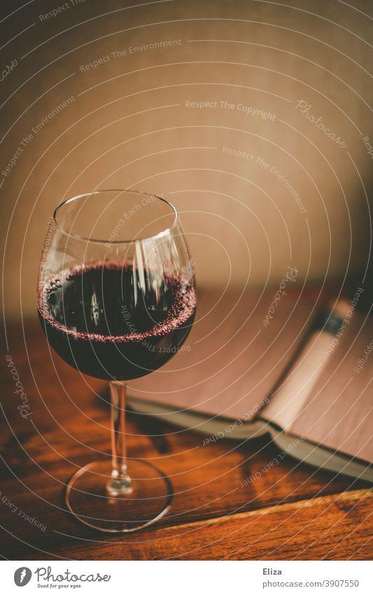 Ein Glas Rotwein und ein aufgeschlagenes Buch. Zeit für sich selber. Wein lesen Weinglas Entspannung Alkohol genießen Rotweinglas