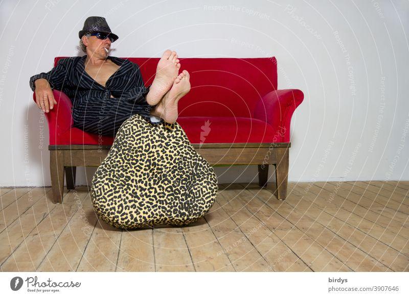 Mann im Anzug mit Hut Sonnenbrille und Zigarette lümmelt lässig auf einem roten Sofa, barfuß cool sitzen lümmeln rotes Sofa bequem chillen Lifestyle müßiggang