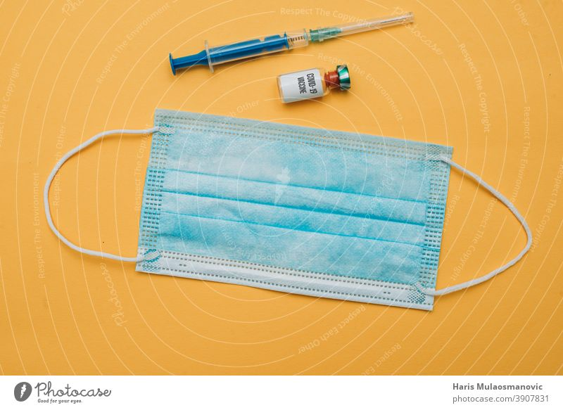 covid-19-Impfstoffnadel und Gesichtsmaske auf gelbem Hintergrund isoliert blau Konzept Textfreiraum Coronavirus Coronavirus-Impfstoff Kur Krankheit Seuche