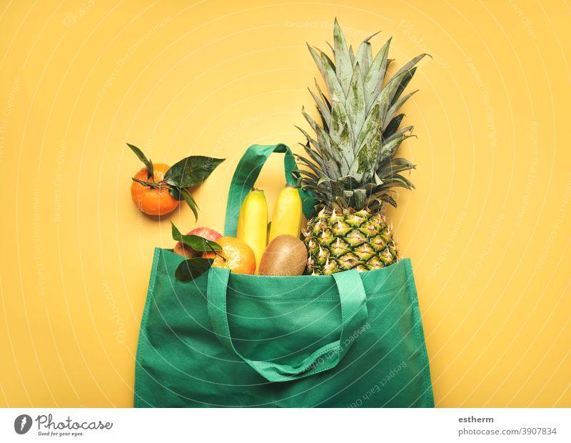 grüne Einkaufstasche mit verschiedenen Früchten, Ananas, Bananen, Orangen, Kiwis und Äpfeln Obstladen Saft Zutaten Veganer Produkte kiwis Apfel Diät Bestandteil