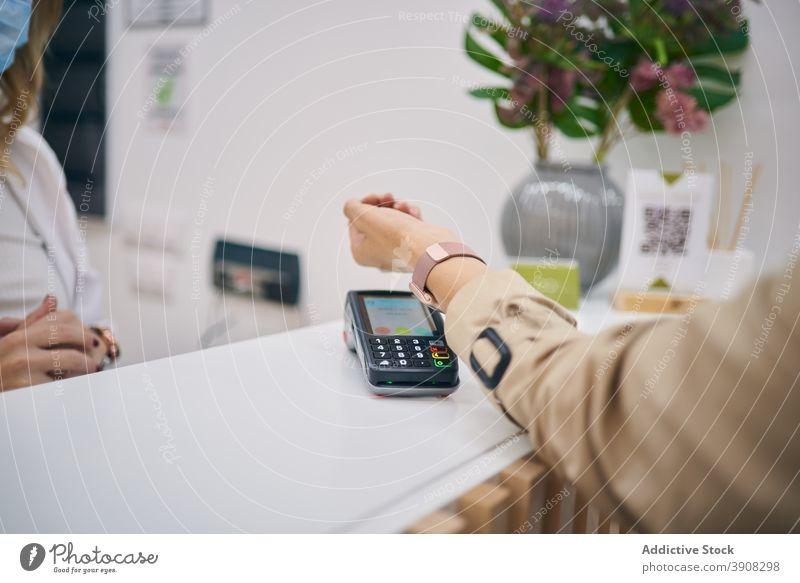 Crop-Frau bezahlt mit Smartwatch im Schönheitssalon intelligente Uhr bezahlen Zahlung pos Terminal Armbanduhr Klient Kauf Transaktion berührungslos nfc Drahtlos
