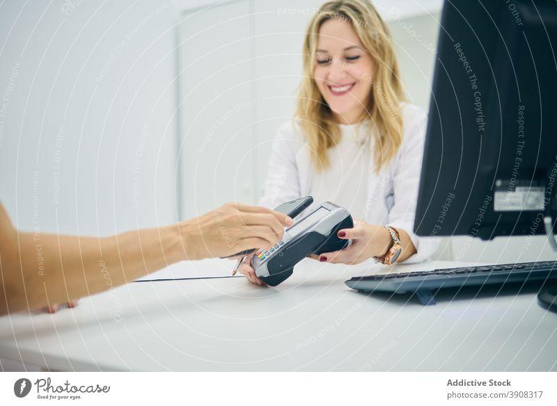 Person bezahlt mit Smartphone in Schönheitsklinik Zahlung bezahlen nfc Terminal Klinik berührungslos Kosmetikerin Kauf Kunde Klient Dienst Zentrum Apparatur