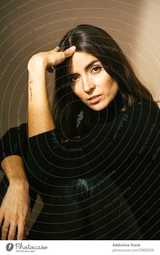 Stilvolle Frau in schwarzer Kleidung und Hut trendy Leder selbstbewusst jung Tattoo informell Vorschein Outfit Kopfbedeckung Kleidungsstück unabhängig