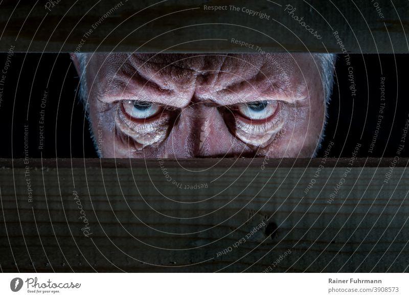 Ein Mann sieht böse durch eine Absperrung aus Holz Porträt Auge Mensch Blick Gesicht Angst Freak Gewalt Aggression Ärger Wut dunkel herzlos Neugier Neugierde