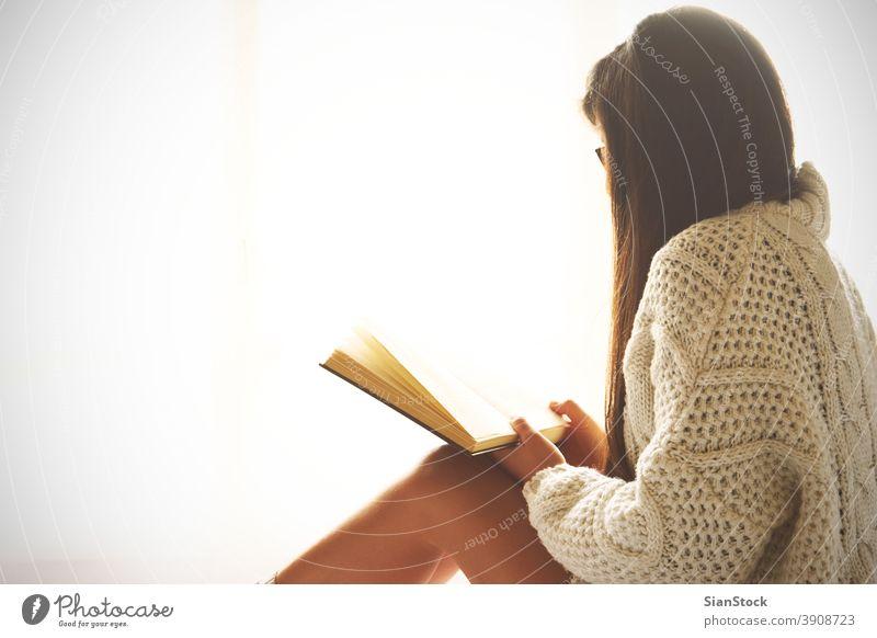Junge Frau sitzt im Bett und liest ein Buch lesen Fenster Ansicht LAZY Sonntag Winter Kaffee Tasse Tee Brille Morgen Mädchen heimwärts sich[Akk] entspannen