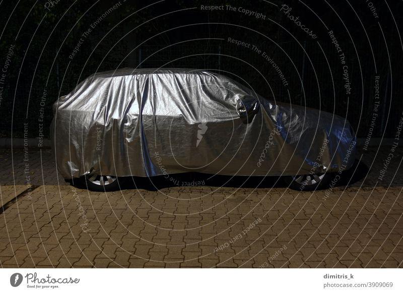Auto mit Schutzhülle bei Nacht PKW Silber schützend Deckung Wetter Gewebe reflektierend Fahrzeug Automobil wasserbeständig wasserdicht bedeckt geparkt Straße