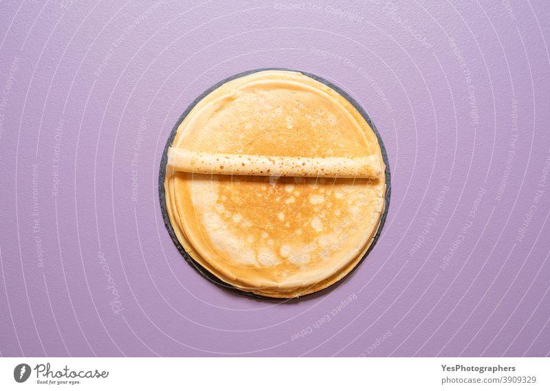 Hausgemachte französische Crêpes, oben Ansicht auf violettem Hintergrund. obere Ansicht gebacken Bäckerei blini Frühstück Komfortnahrung Küche ausschneiden