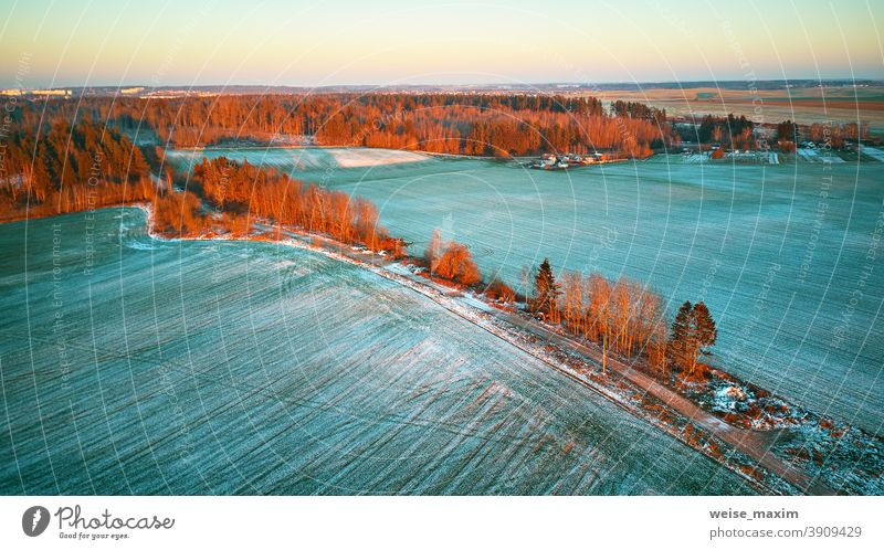 Bunte Bäume im Dezember Sonnenuntergang Luftaufnahme. Ländliche Schotterstraße. Draufsicht auf die Landschaft. Feld Schnee Winter Ernte Antenne Ackerbau Straße