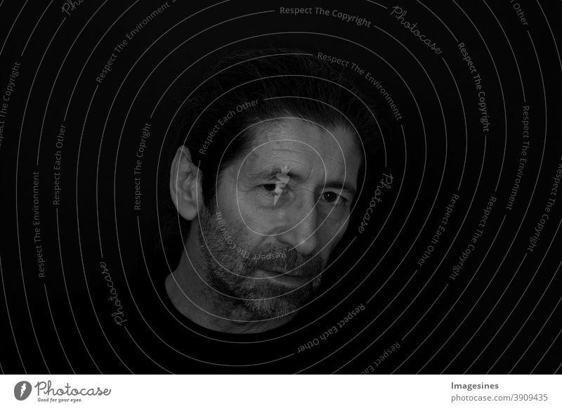 Schwarzweiss Porträt des bärtigen Mannes mit einem kritischen und ernsten Ausdruck auf dunklem schwarzem Hintergrund. Porträt des denkenden wütenden Mannes.