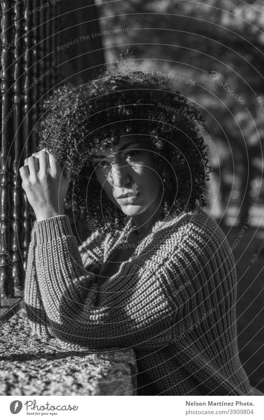 Graustufenaufnahme einer schönen Frau mit lockigem Haar, die in der Nähe eines Metallzauns steht. Porträt Schwarzweißfoto Afro-Look Frisur schwarz jung lässig