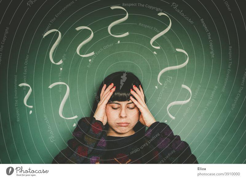 Junge Frau mit vielen Fragezeichen. Unentschlossenheit und Ratlosigkeit. Orientierungslos ratlos Verwirrung Fragen Sorge Ungewisse Zukunft Ungewissheit unsicher