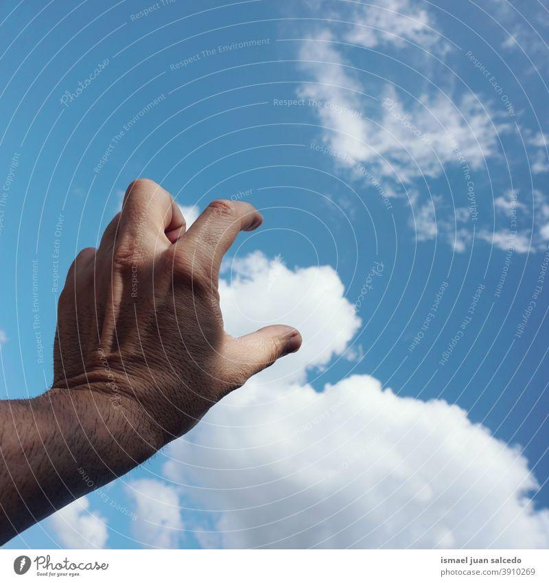 Hand und Wolken Arme Finger Haut Handfläche Körperteil Himmel blau berührend Gefühl erreichend Zeigen Erreichen gestikulieren gestikulierend Konzept Freiheit