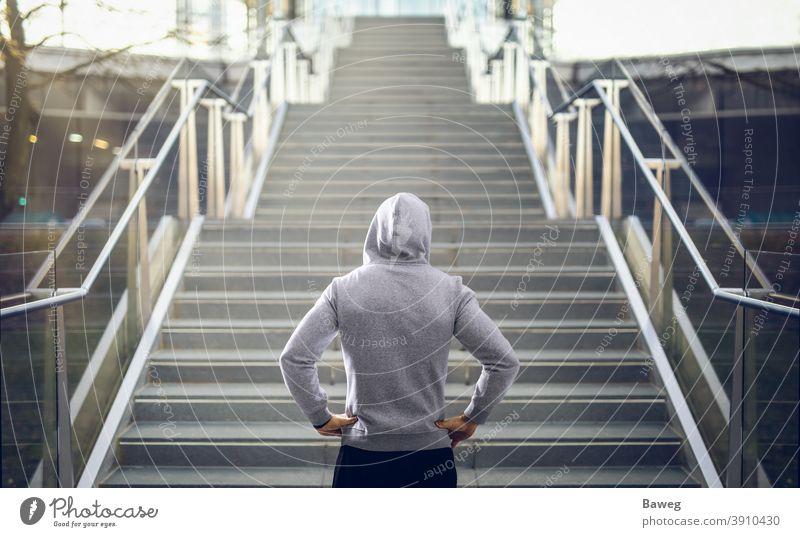 Mann im Kapuzenpulli bereitet sich auf Treppenlauf vor. rennen im Freien Textfreiraum Diät disziplinieren Energie Fitness Gesundheit außerhalb Kraft Sport