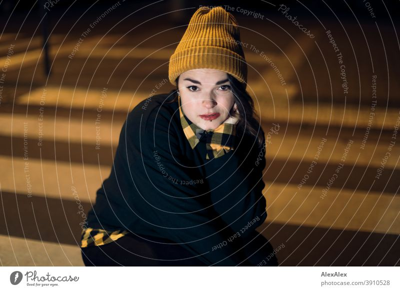 Junge Frau mit Mütze hockt nachts angeleuchtet in orangem Laternenlicht auf einem Zebrastreifen in der Stadt Dschungel Jugendliche Straße Draussen Korkenzieher